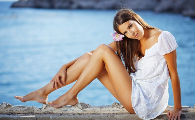 Beautiful female with slim legs posing over sea view